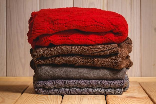 Pilha de camisolas de malha em fundo de madeira