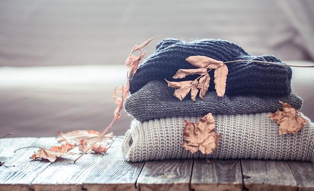 Pilha de camisolas de malha em uma mesa de madeira