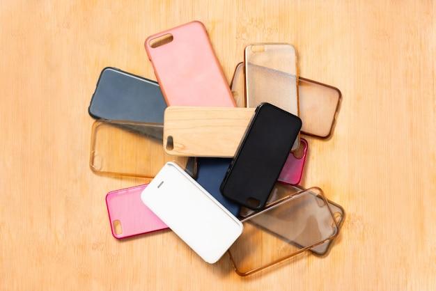 Pilha de capas traseiras de plástico multicoloridas para telefones celulares na mesa de madeira