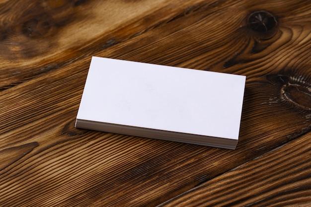 Pilha de cartões de visita brancos sobre fundo de madeira marrom