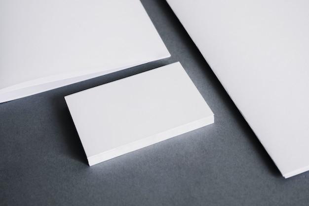 Pilha de cartões de visita em branco ao lado de papéis