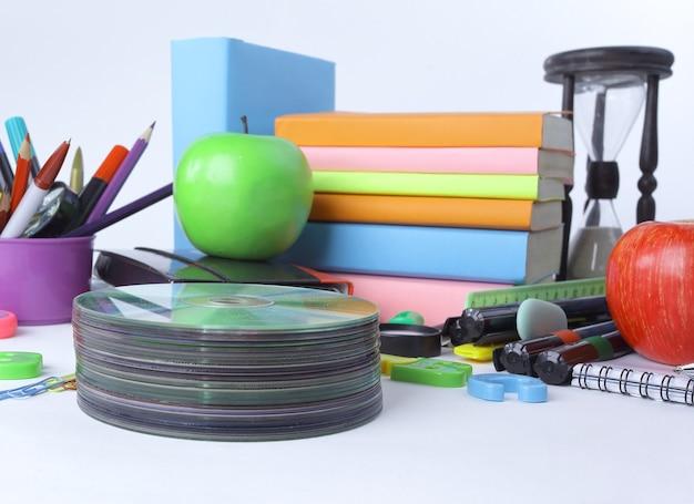Pilha de cds e material escolar isolado no branco