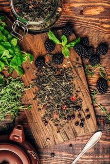 Pilha de chá verde seco e amoras frescas na tábua de madeira
