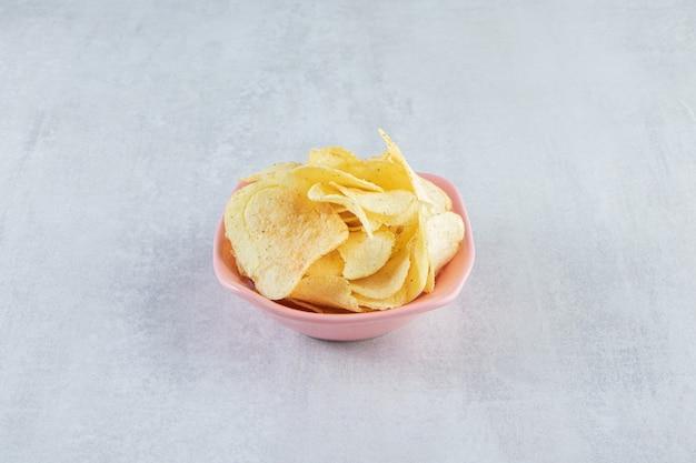 Pilha de chips crocantes salgados colocados em uma tigela rosa na pedra.