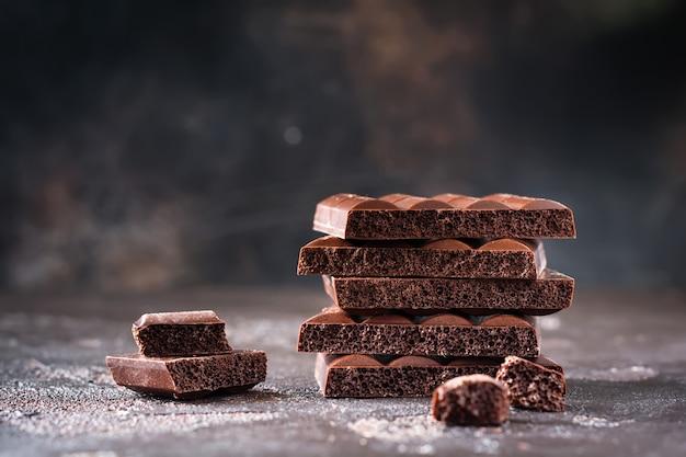 Pilha de chocolate amargo poroso e arejado na superfície escura e velha. foco seletivo.