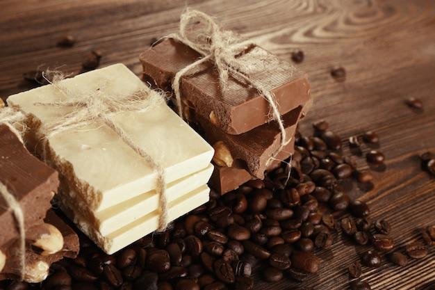 Pilha de chocolate amarrado com grãos de café na mesa de madeira, closeup
