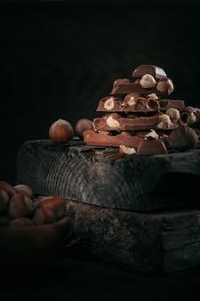 Pilha de chocolate com leite de avelã e nozes em fundo escuro