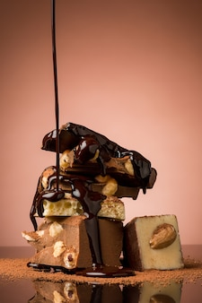 Pilha de chocolate quebrado na mesa contra o fundo marrom do estúdio e spray de chocolate quente