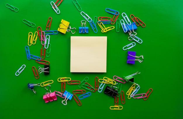 Pilha de clipes de papel isolados em um fundo verde, documentos, conceito de material de escritório, mesa de escritório suja. lugar vazio para escrita e texto. vista superior, layout. colocação plana.