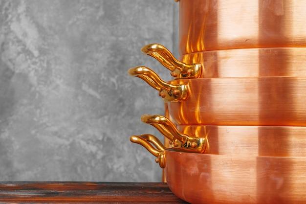 Pilha de cobre panelas na mesa de madeira fechar