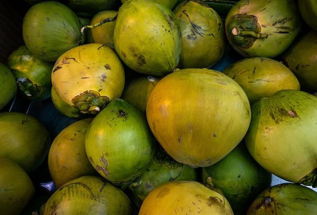 Pilha de coco verde no mercado. mercado de alimentos de agricultores tradicionais asiáticos nas linhas coloridas de frutas e legumes. frutas frescas nas ruas em taiwan. cocos dispostos na barraca para venda.