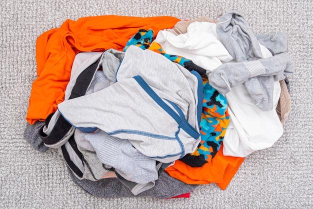 Pilha de coisas sujas, roupa suja, camiseta, meias, calças, cuecas no chão no banheiro