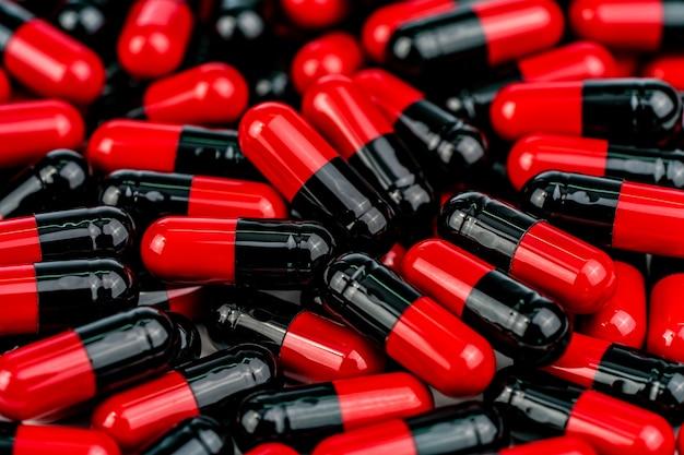 Pilha de comprimidos cápsula vermelho-preto. conceito de resistência aos antibióticos. comprimidos de cápsulas antimicrobianas. indústria farmacêutica.