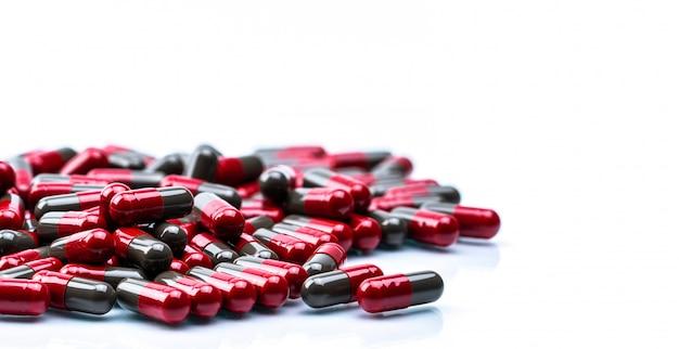 Pilha de comprimidos cápsula vermelhos e cinza isolados