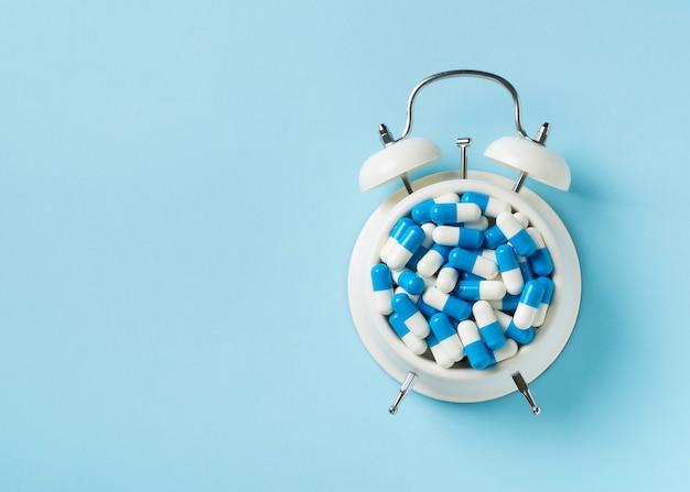 Pilha de comprimidos e cápsulas e despertador em azul. tempo e conceito de saúde. vista do topo