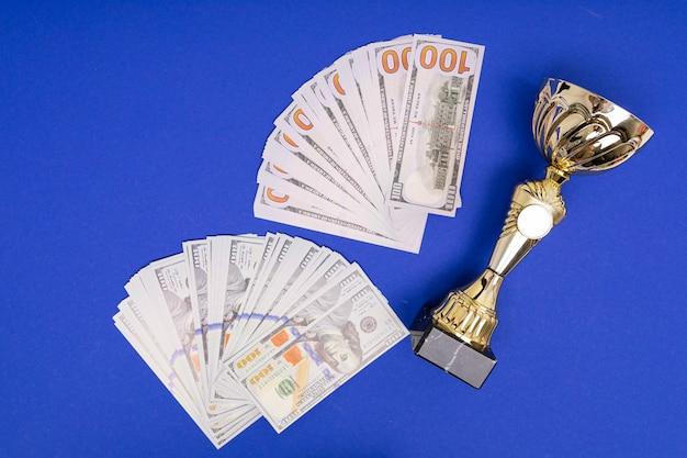 Pilha de copo de dinheiro e vencedor no fundo da mesa azul puro