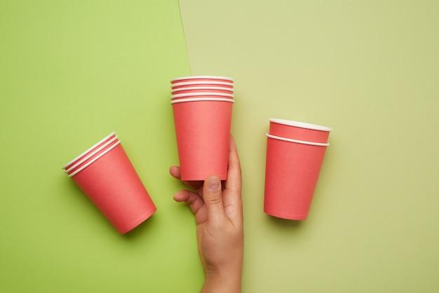 Pilha de copos descartáveis de papel vermelho sobre fundo verde, conceito ecológico, desperdício zero