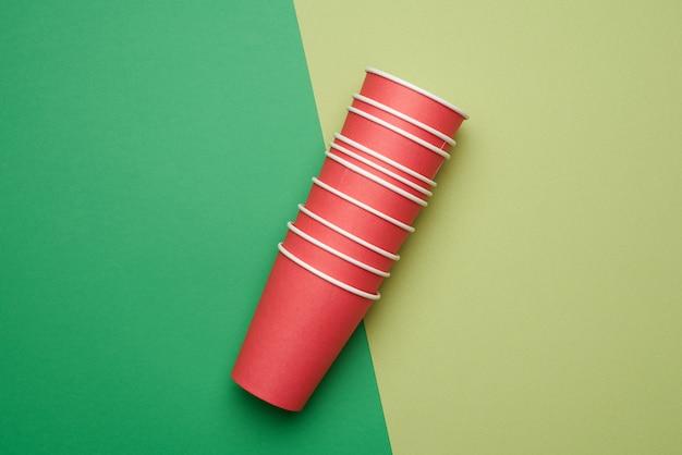 Pilha de copos descartáveis de papel vermelho sobre um fundo verde, plano
