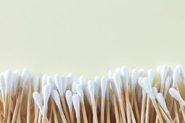 Pilha de cotonetes ou botões de bambu com vista superior na superfície bege, copie o espaço