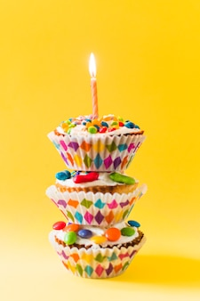 Pilha de cup cakes decorativos com vela acesa em fundo amarelo