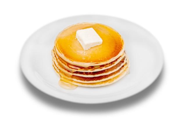 Pilha de deliciosas panquecas com manteiga em um prato branco