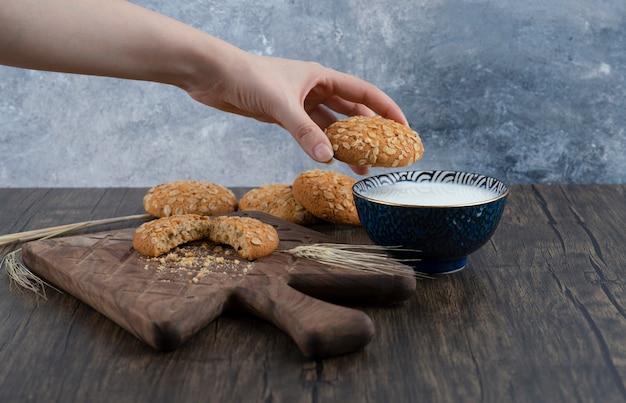 Pilha de deliciosos biscoitos com cereais e uma tigela de leite fresco.