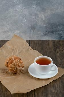 Pilha de deliciosos biscoitos de aveia e uma xícara de chá na mesa de madeira.