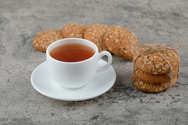 Pilha de deliciosos biscoitos de aveia e uma xícara de chá na superfície de mármore.