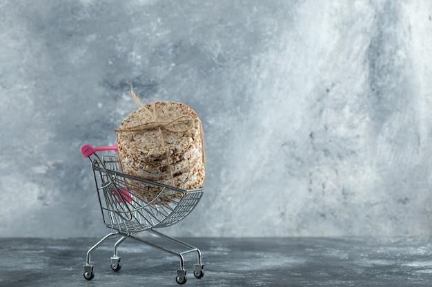 Pilha de deliciosos pães crocantes em um pequeno carrinho de compras