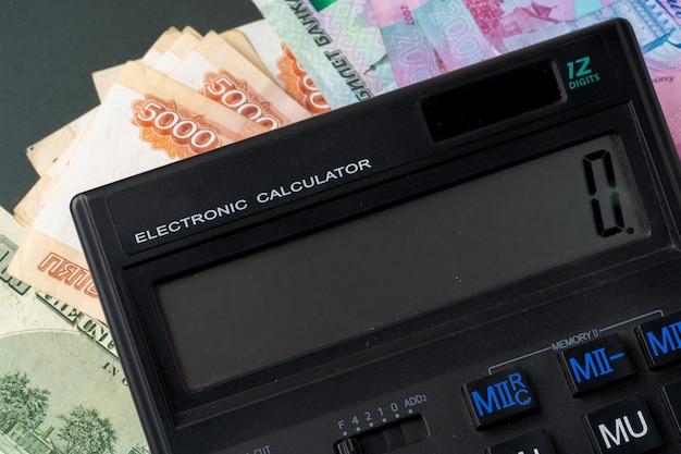 Pilha de dinheiro close-up, três moedas de dólares americanos, rublos russos e hryvnias ucranianos