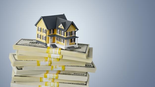 Pilha de dinheiro com a casa no fundo