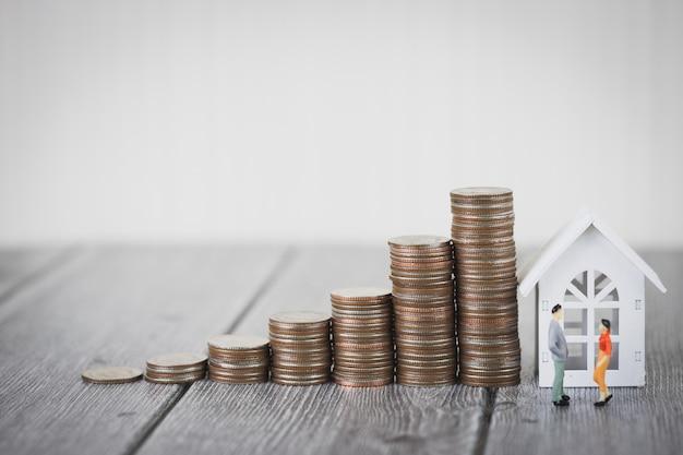 Pilha de dinheiro de moeda intensificar com casa branca, investimento de propriedade e hipoteca de casa financeira