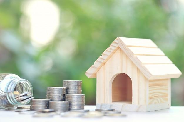 Pilha de dinheiro de moedas e casa modelo