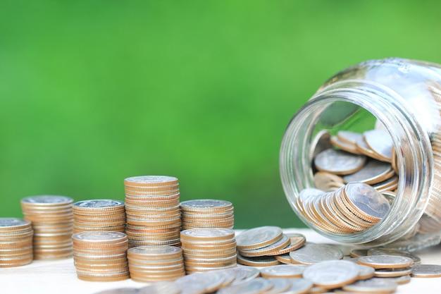 Pilha de dinheiro de moedas e garrafa de vidro em verde natural