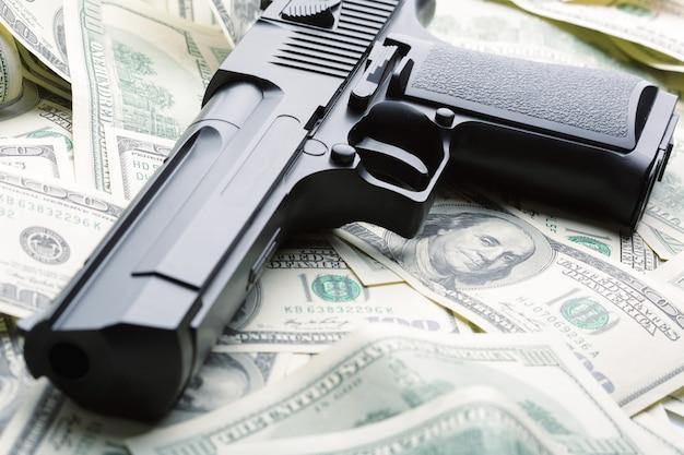 Pilha de dinheiro e arma