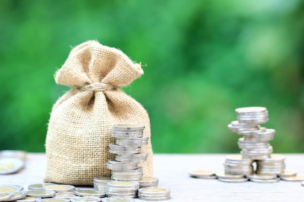 Pilha de dinheiro moedas e um saco sobre fundo verde natural, crescimento do investimento empresarial e economizar dinheiro para preparar no futuro conceito
