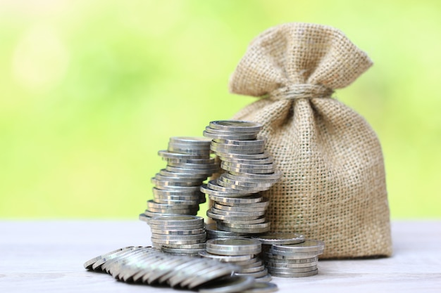 Pilha de dinheiro moedas e um saco sobre fundo verde natural, crescimento do investimento empresarial e poupar dinheiro para preparar no futuro conceito, finanças