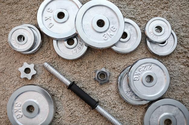 Pilha de discos de halteres de cromo brilhante deitado ao redor do aperto