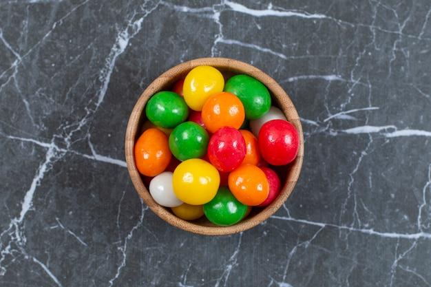 Pilha de doces coloridos em uma tigela de madeira.