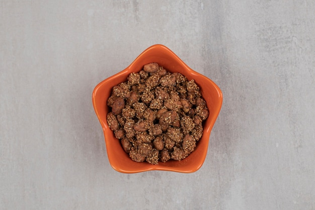 Pilha de doces com sementes de gergelim em uma tigela de laranja.