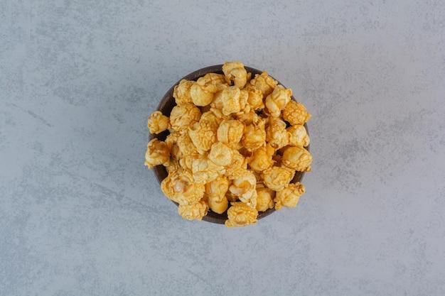 Pilha de doces de pipoca em uma tigela pequena na superfície de mármore