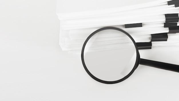 Pilha de documentos em papel de relatório com lupa. conceito de negócio e pesquisa.