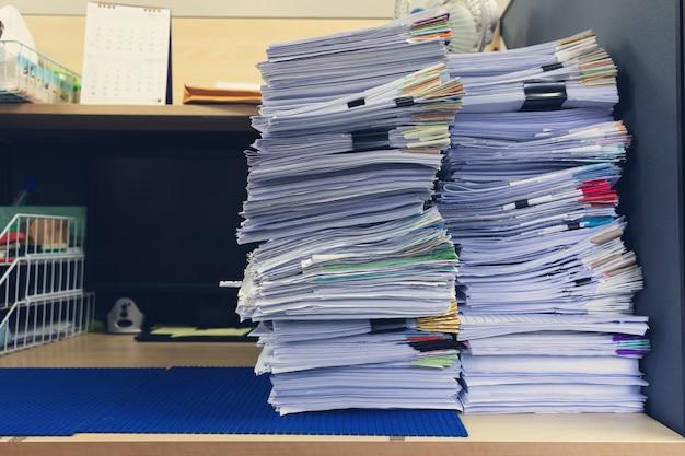 Pilha de documentos inacabados na mesa de escritório