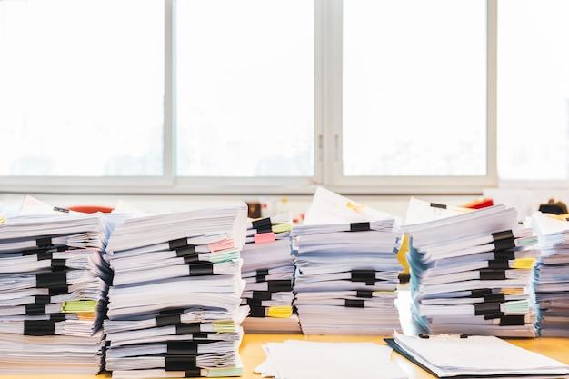 Pilha de documentos inacabados na mesa de escritório.