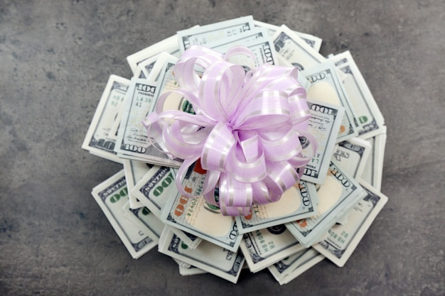 Pilha de dólares com arco como presente na mesa texturizada cinza