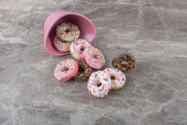 Pilha de donuts e uma tigela caída na superfície de mármore