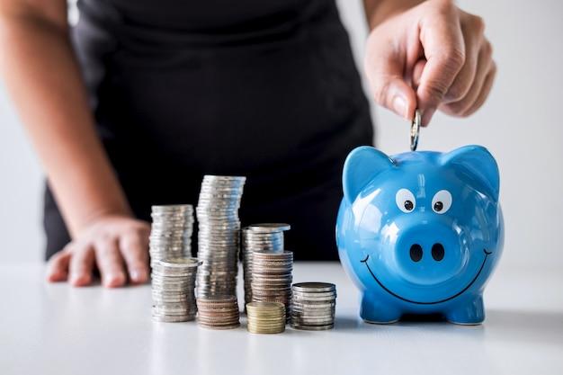 Pilha de empilhamento e mão colocando moeda no cofrinho para o planejamento passo até crescer