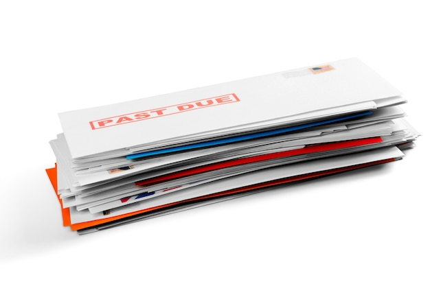 Pilha de envelopes com contas de serviços públicos em atraso isoladas em branco