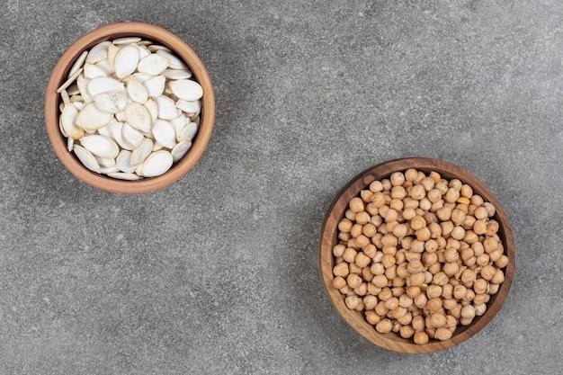 Pilha de ervilhas amarelas e sementes de abóbora em tigelas de madeira.