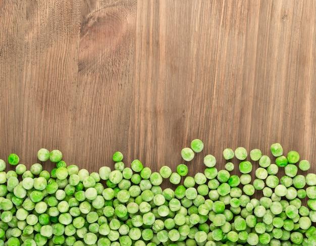 Pilha de ervilhas verdes doces congeladas em um fundo de madeira, vista superior com copyspace